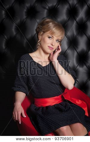 Girl In Black Dress Sitting On A Red Chair