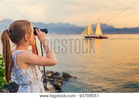 Outdoor portrait of a cute little girl playing by the lake