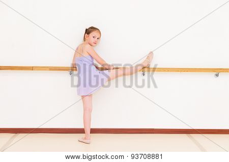 Little ballerina in a dance school, wearing purple dance dress