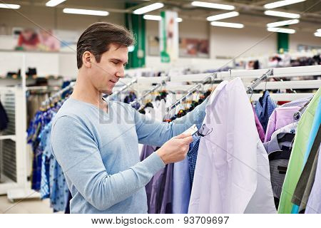 Man Looking At Price Tag Of Goods