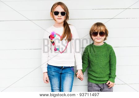 Fashion kids outdoors, wearing pullovers and sun glasses