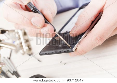 Serviceman repairing mobile phone in the electronic workshop