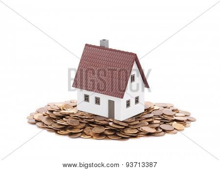 House miniature with pile of coins