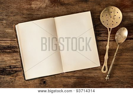 Empty menu or cookbook and vintage kitchen utensils on wooden table