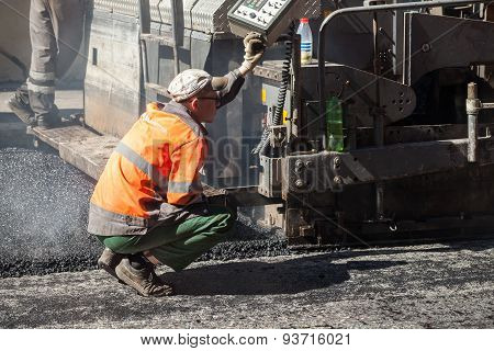 Operator Of Paver Works On A Control Panel