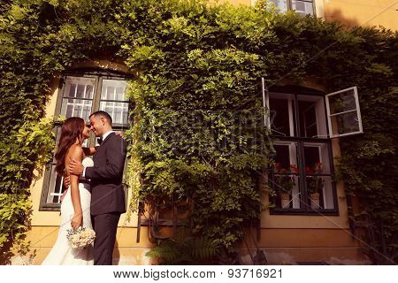 Bride And Groom Embracing In Front Of A Beautiful House Covered With Ivy