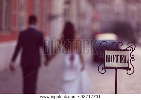 Old Hotel Sign With Bride And Groom In The Background As Silhouettes