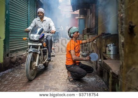 VARANASI, INDIA - 20 FEBRUARY 2015: Street vendor makes fire for milky tea in coal oven while motorcyclist passes by.