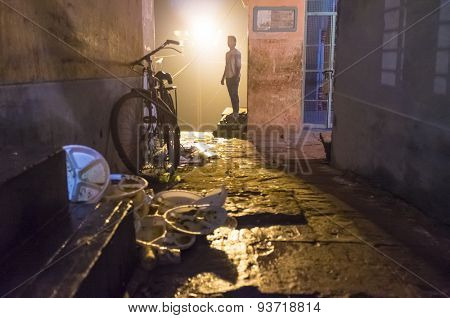 VARANASI, INDIA - 19 FEBRUARY 2015: Adult man in street with parked bicycle and leftover trash from street vendor. Every morning garbage is cleaned from streets by locals or garbage-men.