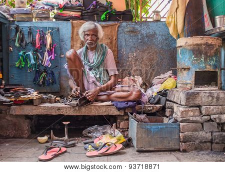VARANASI, INDIA - 25 FEBRUARY 2015: Indian vendor sits in street shop and repairs slippers.