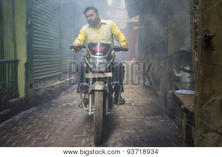 VARANASI, INDIA - 20 FEBRUARY 2015: Man on motorcycle passes through street filled with smoke. Coal ovens are used as source of heat for making milky tea.