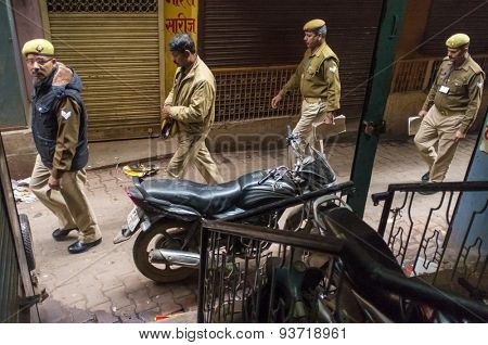 VARANASI, INDIA - 20 FEBRUARY 2015: Four Indian policemen walk on street of old part of Varanasi and pass by parked motorcycle.