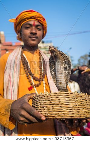 VARANASI, INDIA - 23 FEBRUARY 2015: Indian boy dressed up in religious clothes holds cobra in basket.