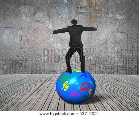 Businessman Balancing On The Colorful Symbols Ball