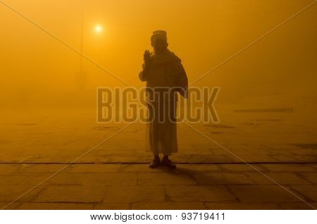 VARANASI, INDIA - 20 FEBRUARY 2015: Pilgrim salutes on Varanasi ghat on foggy morning. Millions of pilgrims come to Varanasi every year to bath in the holy River Ganges.