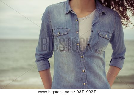 Slim Woman In A Denim Shirt And White T-shirt Stands On The Beach Against The Sea