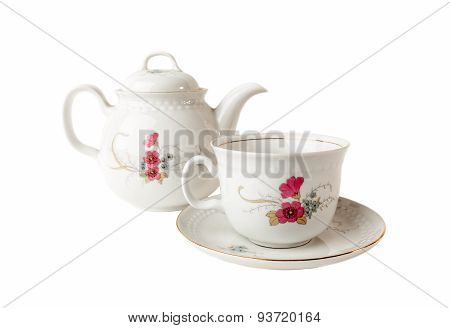 Porcelain teapot, teacup and saucer with floral patterns isolated over white