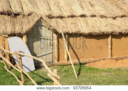 Clay House With A Thatched Roof And Shield Alongside Door