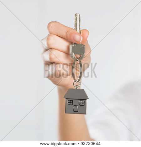 Closeup shot of a woman holding key of her new house. Woman buying new home and showing key. Shallow depth of field with focus on house key.