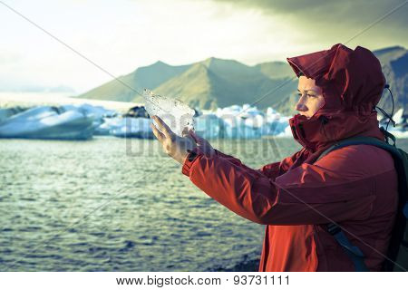 Woman is holding a piece of ice from the glacier at Jokulsarlon Lagoon in Iceland. Cross-processed treatment