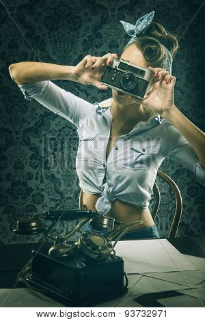 Vintage woman in old-fashioned dress holding old camera