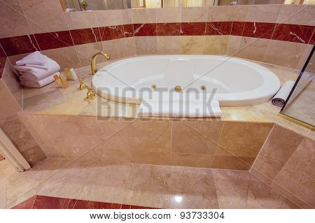 White Jacuzzi Bathtub Decorated With Marble Tiles