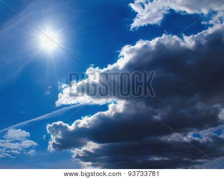 Dark Fluffy Clouds In Sunlight On Background Of Blue Sky