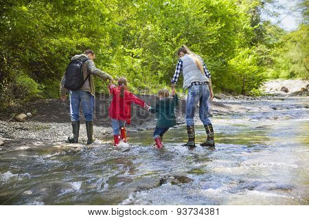 Young Family With Two Little Daughters On Mountain Trek