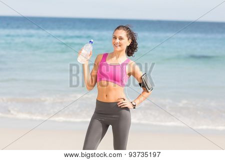 Pretty fit woman looking at camera at the beach