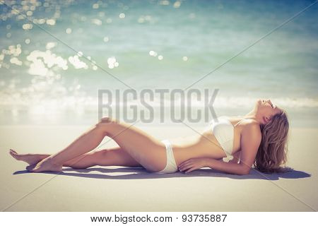 Lying pretty woman in swimsuit tanning on beach