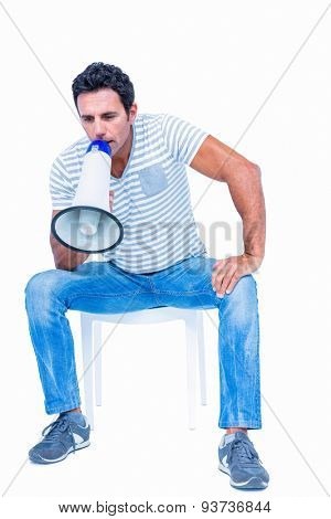 Sitting man shouting through megaphone on white background