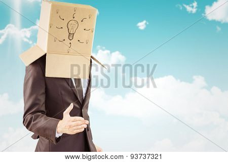 Anonymous businessman offering his hand against blue sky