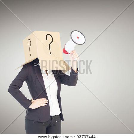 Anonymous businesswoman holding a megaphone against grey vignette