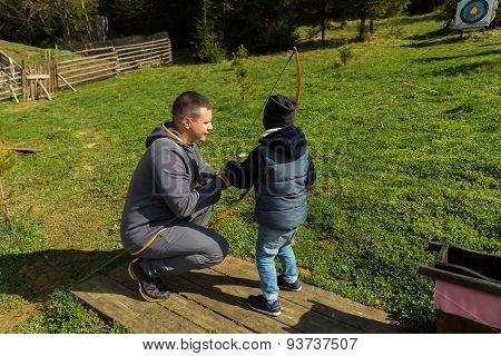Dad teaches his son to shoot a bow