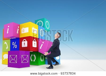Businessman in suit carrying something against blue sky