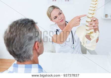 Doctor explaining anatomical spine to her patient in medical office