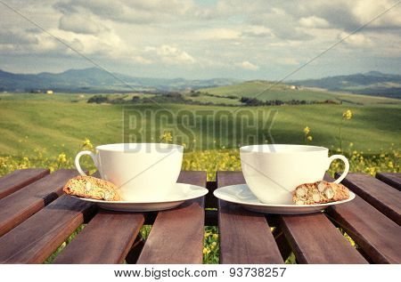 Filtered image of two coffee cups and cantuccini on the wooden table against Tuscan landscape, Italy