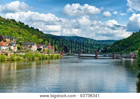 Bridge over the Neckar River near Heidelberg, Germany with houses grouped along the river bank in a picturesque sunny landscspe with a blue sky and clouds