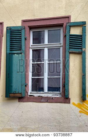 Neglected Building in Need of Repairs, Architectural Detail of Window with Broken Green Shutters and Yellow Graffiti on Wall