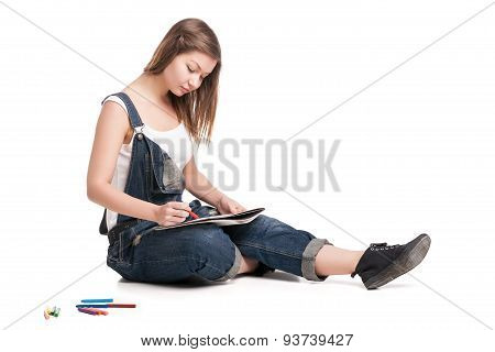 Young woman happily sitting  on the floor drawing in her note pad