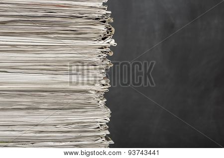 A Pile Of Newspapers In Front Of A Chalkboard