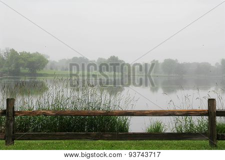 Wooden Fence Framing Lake On Rainy Day