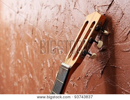 Classical acoustic guitar on brown wall background