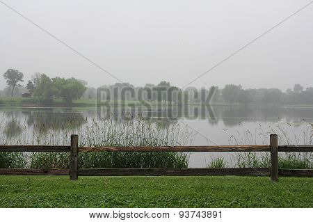 Hazy Rainy Day With Fence And Lake
