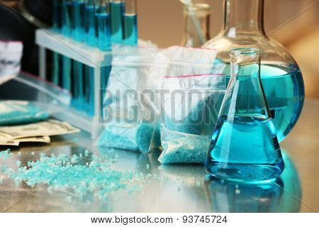 Blue methamphetamine and liquid in flasks on table in laboratory