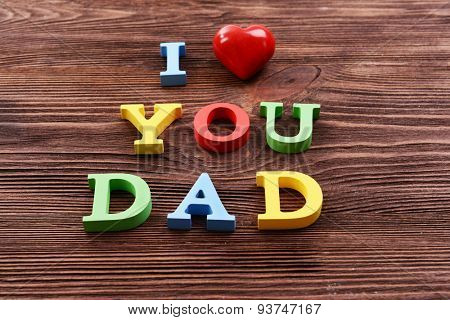 Inscription I LOVE YOU DAD made of colorful letters on wooden background
