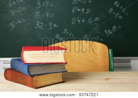 Stack of books on desk, on blackboard background