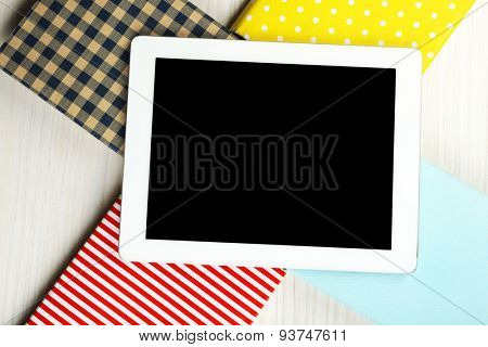 Notebook on top of pile of books  on wooden background