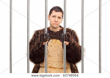 Studio shot of a sad young man in a bear costume standing behind bars in a cell isolated on white background