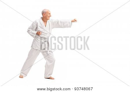 Full length profile shot of an old man in a white kimono practicing karate isolated on white background